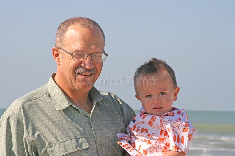 Grandfather and grandson at beach stock photo