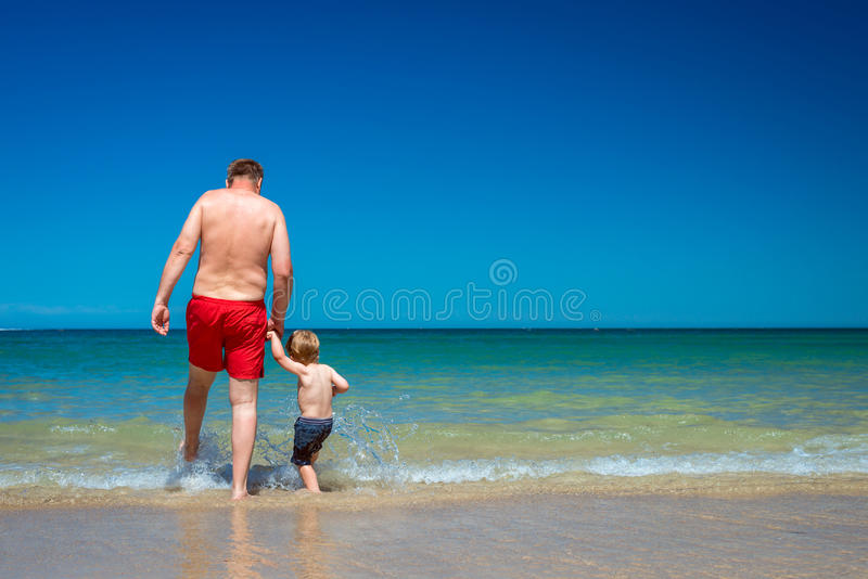 Grandfather with grandson on beach stock photo