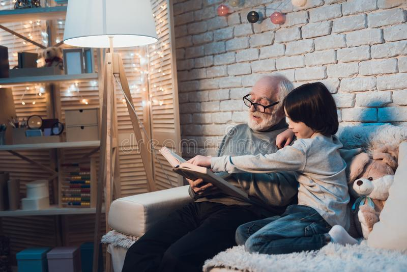 Grandfather and grandson at night at home. Granddad is reading fairy tales book. Grandfather and grandson on couch at night at home. Granddad is reading fairy stock images