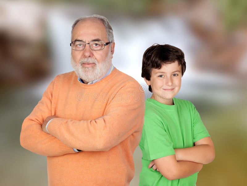 Grandfather and grandson with crossed arms and unfocused background stock images