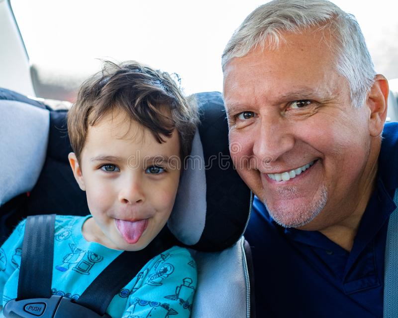 Grandfather and grandson. Cute boy sitting in a car seat with his grandfather having fun stock photo