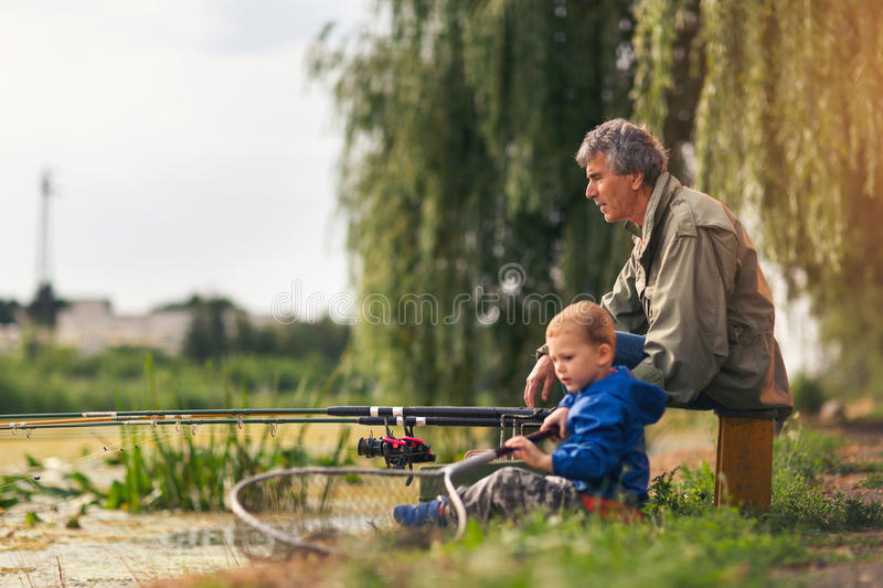 Grandfather with a grandson on feshwater fishing. royalty free stock images