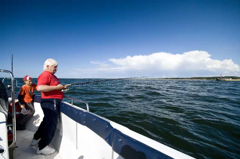 Grandfather, grandson fishing. Grandfather and his grandson fishing at sea (ocean) from a motorboat stock photo