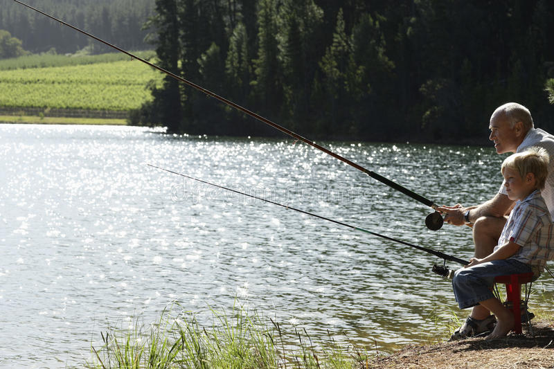Grandfather And Grandson Fishing By Lake. Side view of grandfather and grandson fishing together by lake stock photos