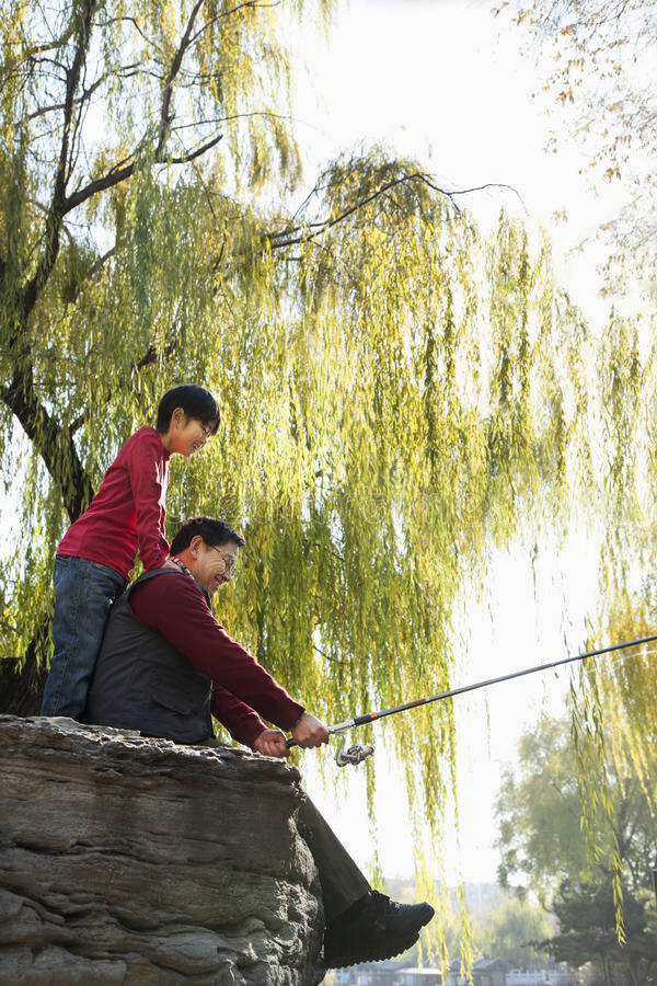 Grandfather and grandson fishing portrait at lake stock images