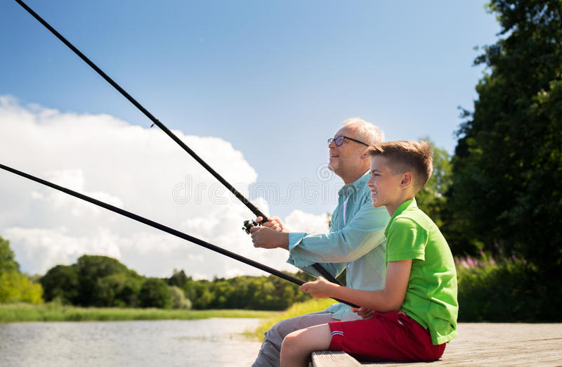 Grandfather and grandson fishing on river berth. Family, generation, summer holidays and people concept - happy grandfather and grandson with fishing rods on stock photos