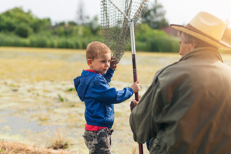 Grandfather with a grandson on freshwater fishing. royalty free stock photo
