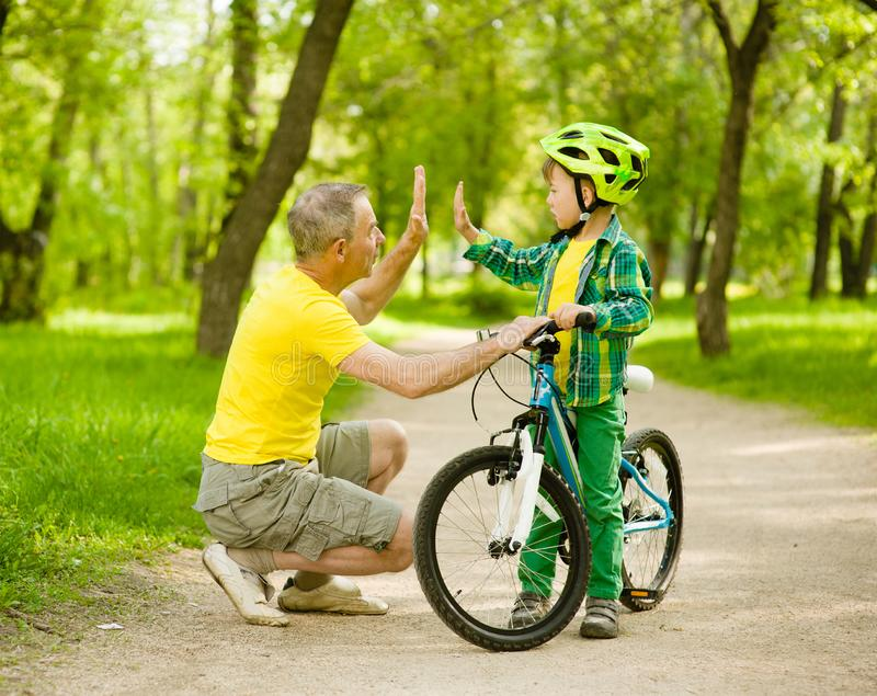 Grandfather and grandson give high five while cycling in the park.  royalty free stock photos