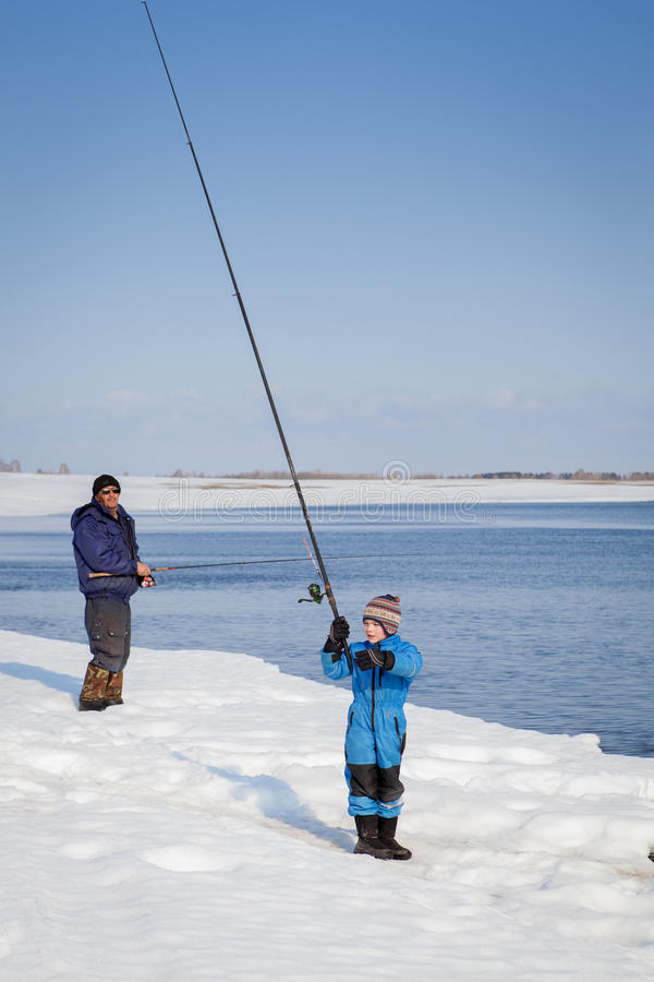 Grandfather and grandson go fishing along river stock photo
