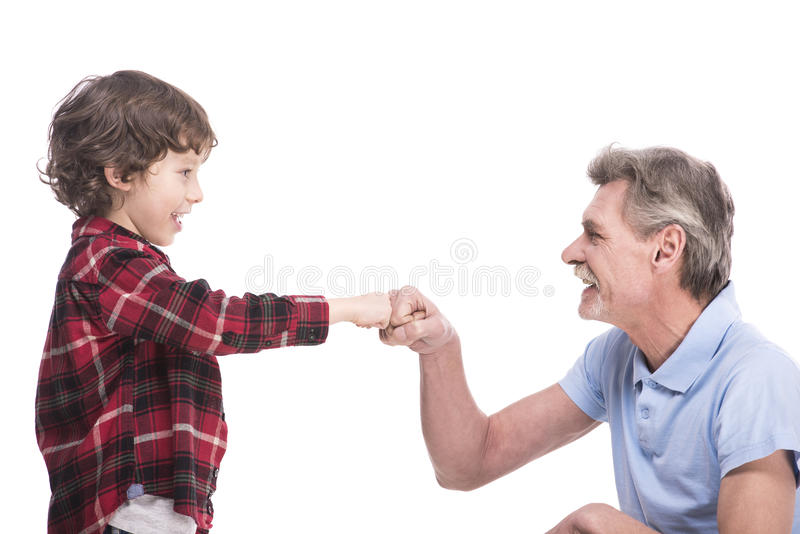 Grandfather and grandson. Good time together. Portrait of a healthy grandfather and his grandson are playing over the white background royalty free stock image
