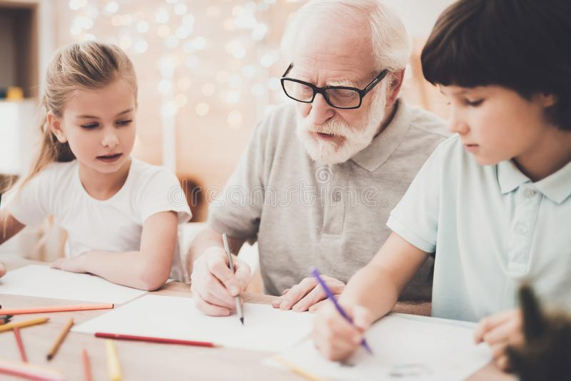 Grandfather, grandson and granddaughter at home. Children are drawing with color pencils. Grandfather, grandson and granddaughter at table at home. Children are stock photography