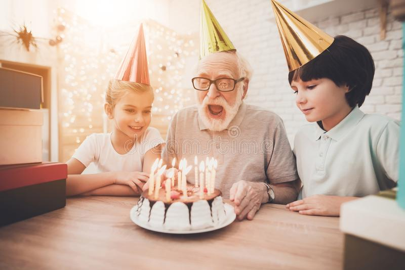 Grandfather, grandson and granddaughter at home. Grandpa is blowing candles on birthday cake. Grandfather, grandson and granddaughter at table at home. Grandpa royalty free stock photos