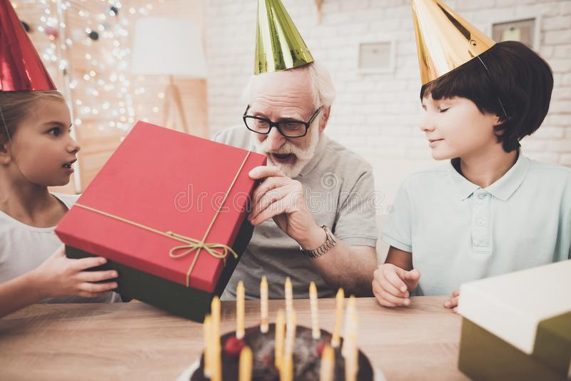 Grandfather, grandson and granddaughter at home. Birthday party. Grandfather, grandson and granddaughter at table at home. Birthday party royalty free stock photos