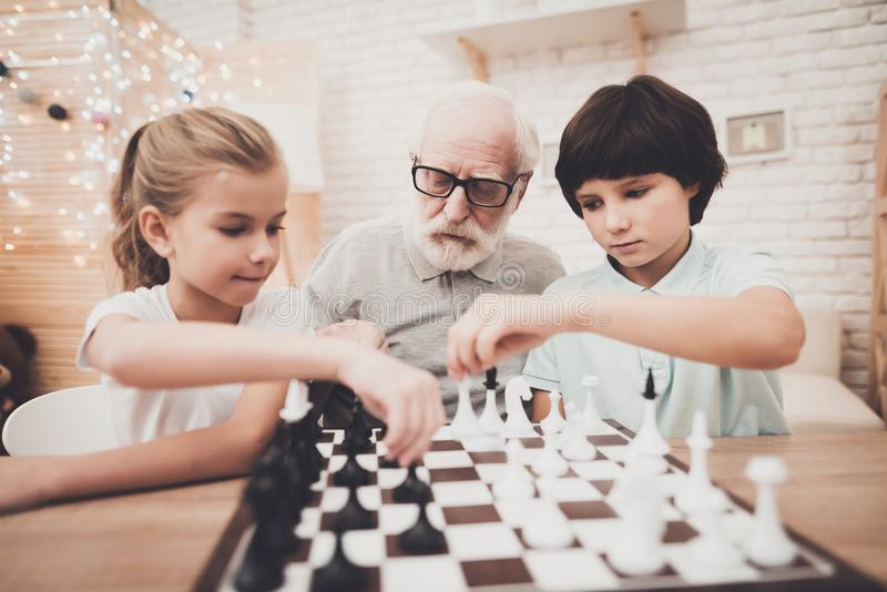 Grandfather, grandson and granddaughter at home. Children and grandpa are playing chess. royalty free stock photo