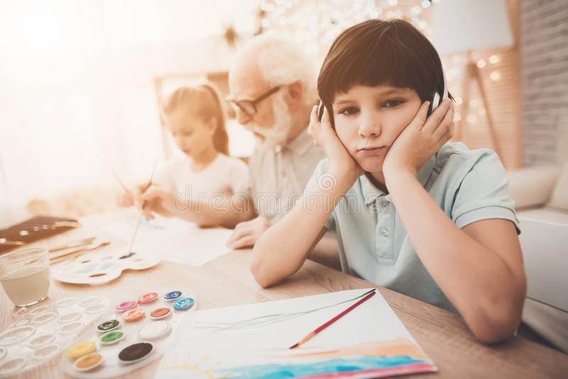 Grandfather, grandson and granddaughter at home. Children are painting and listening to music. Grandfather, grandson and granddaughter at table at home royalty free stock photography