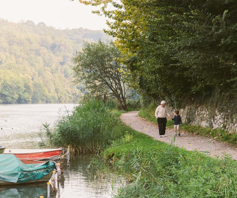 Grandfather and grandson hold hands while walking on a path next to a river in Italy stock images