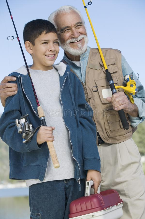 Grandfather and grandson holding fishing rods royalty free stock images
