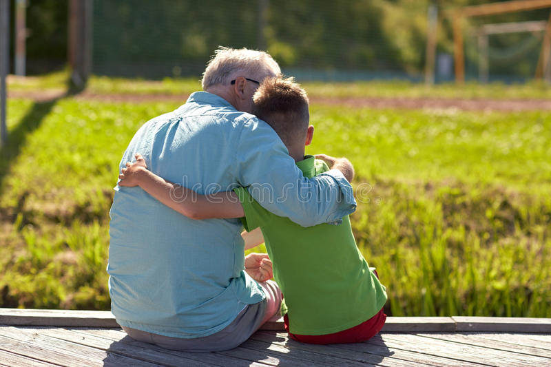 Grandfather and grandson hugging on berth. Family, generation, relations and people concept - happy grandfather and grandson hugging on berth royalty free stock photo