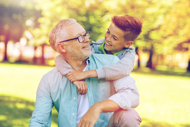 Grandfather and grandson hugging at summer park. Family, generation, relations and people concept - happy grandfather and grandson hugging at summer park royalty free stock photos