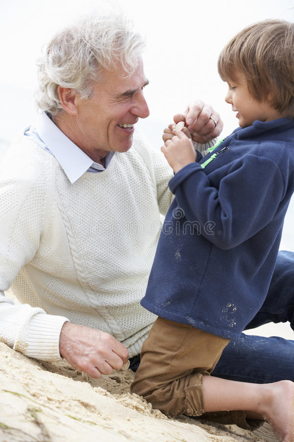 Grandfather And Grandson Looking at Shell On Beach Together royalty free stock image