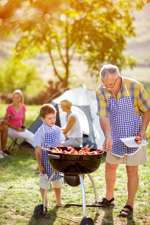 Grandfather and grandson making barbecue royalty free stock image