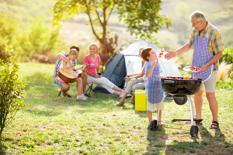 Grandfather and grandson making barbecue royalty free stock photography