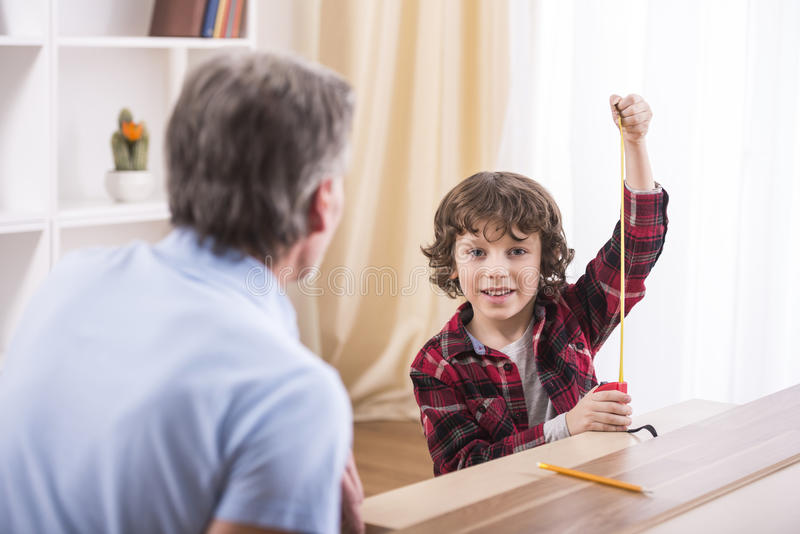 Grandfather and grandson. Are measuring a table with measuring tape stock photo