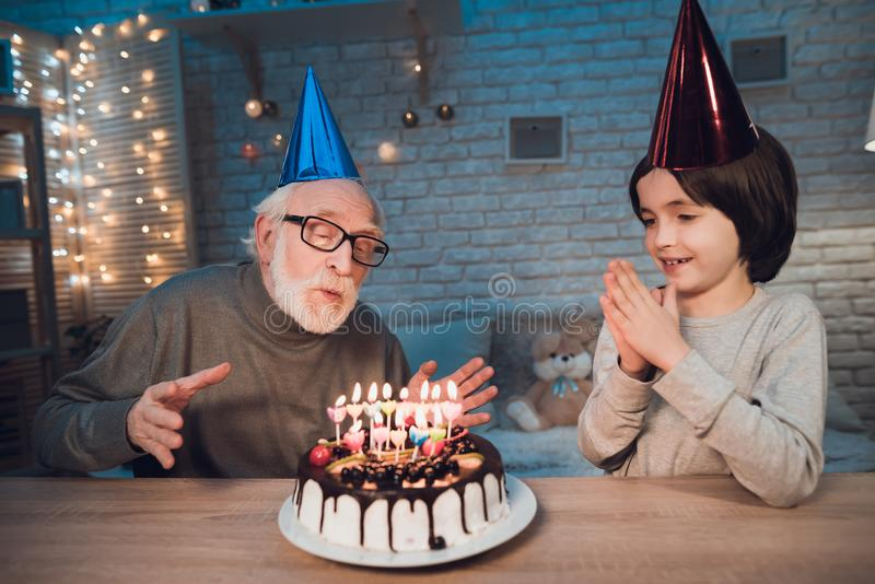 Grandfather and grandson at night at home. Birthday party. Granddad is blowing birthday cake candles. Grandfather and grandson at table at night at home stock photo