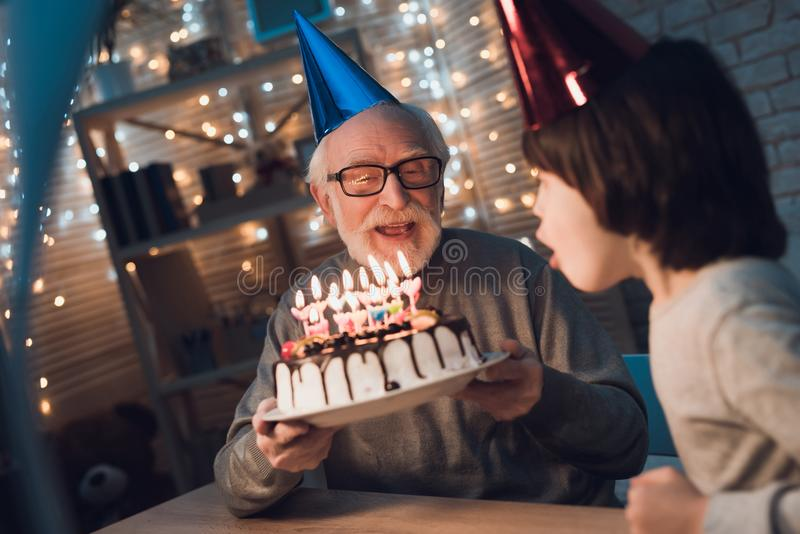 Grandfather and grandson at night at home. Birthday party. Granddad is giving boy birthday cake. stock photo