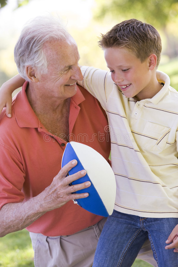 Grandfather and grandson outdoors with football stock images