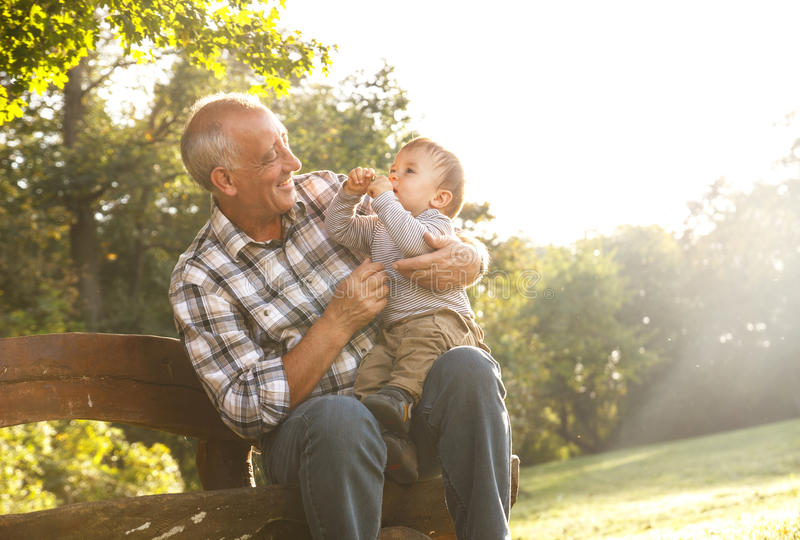 Grandfather with grandson in park. Playful grandfather spending time with his grandson in park stock image