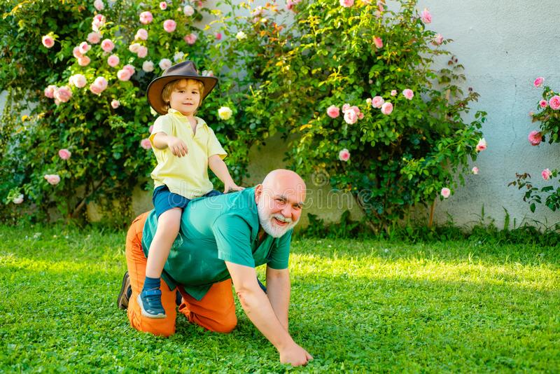 Grandfather and Grandson - piggy back ride. Child with Grandfather dreams in summer in nature. Grandpa retiree. Grandpa stock photography