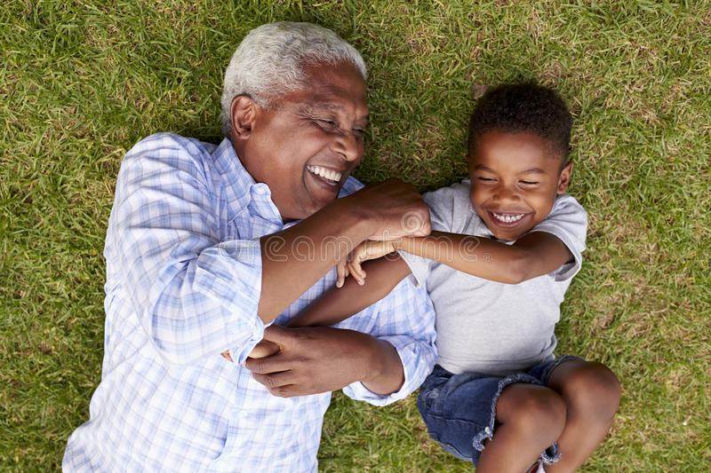 Grandfather and grandson play lying on grass, aerial view royalty free stock image