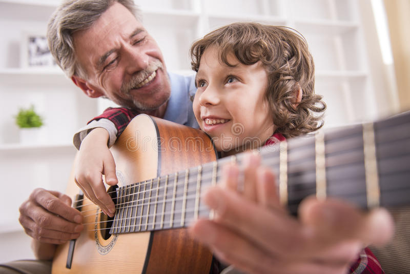 Grandfather and grandson. Grandfather is playing guitar with his grandson royalty free stock photos