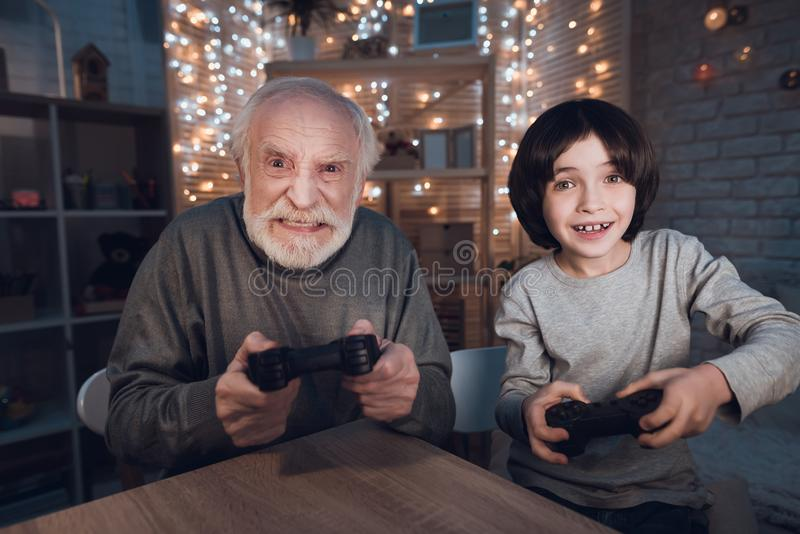 Grandfather and grandson are playing video games at night at home. Grandfather and grandson are playing video games at table at night at home royalty free stock photography