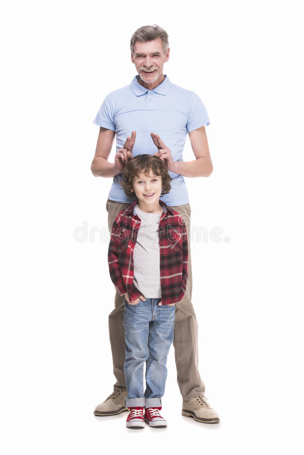 Grandfather and grandson. Portrait of a healthy grandfather and his grandson playing over the white background royalty free stock photos