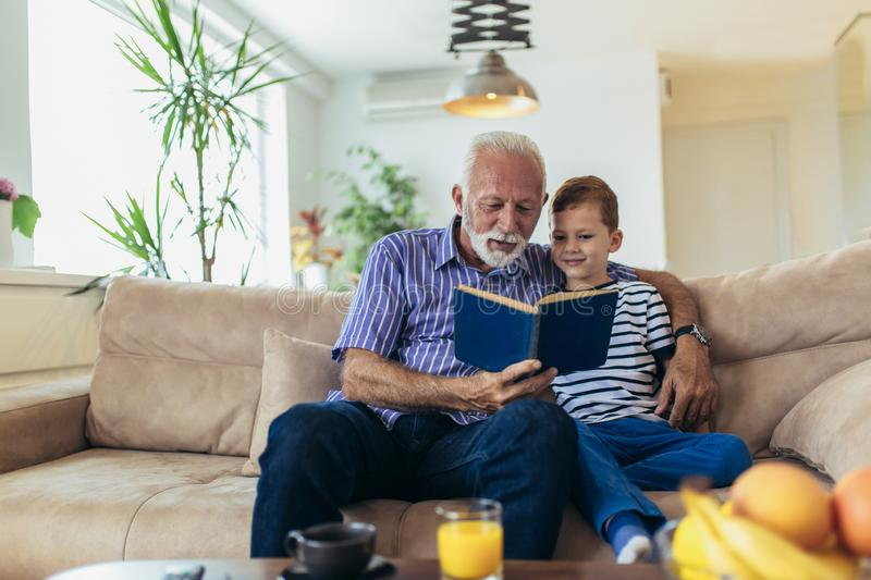 Grandfather With Grandson Reading Together stock images