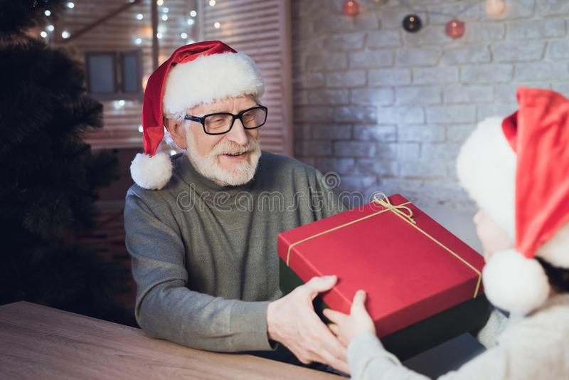 Grandfather and grandson in Santa Claus`s hats at night at home. Granddad is giving boy present. Grandfather and grandson in Santa Claus`s hats at table at stock image
