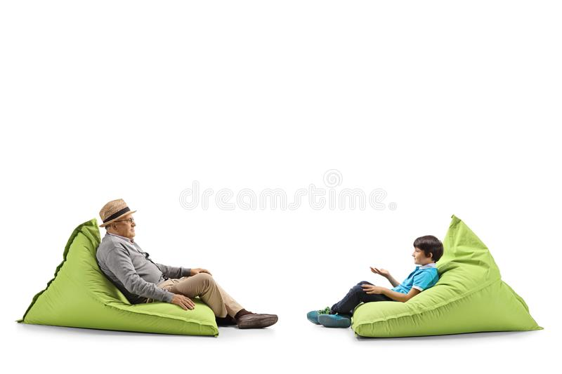 Grandfather and grandson sitting on bean bags royalty free stock image