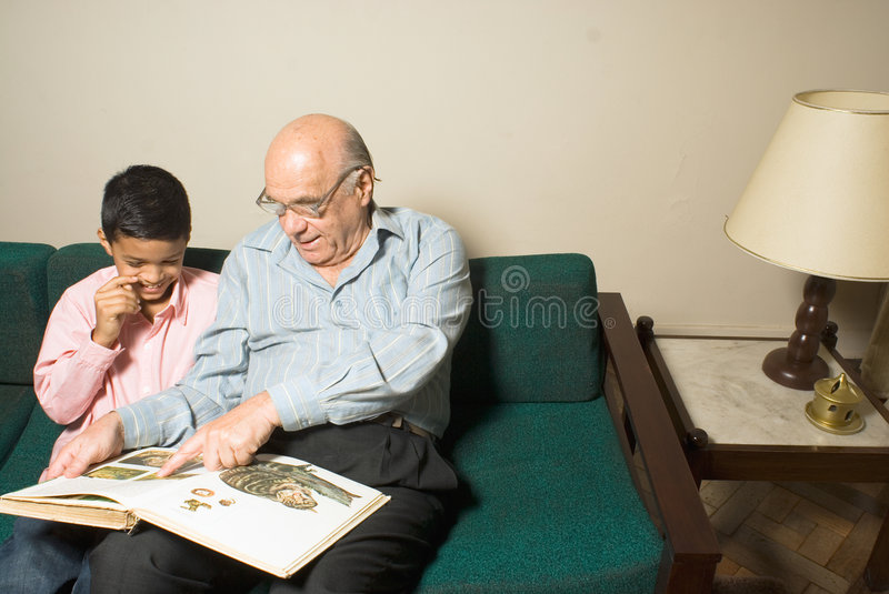 Grandfather and grandson sitting a couch-Hori. Grandfather and grandson sitting on the couch while the grandfather teaches his how to read. The grandfather is stock photos