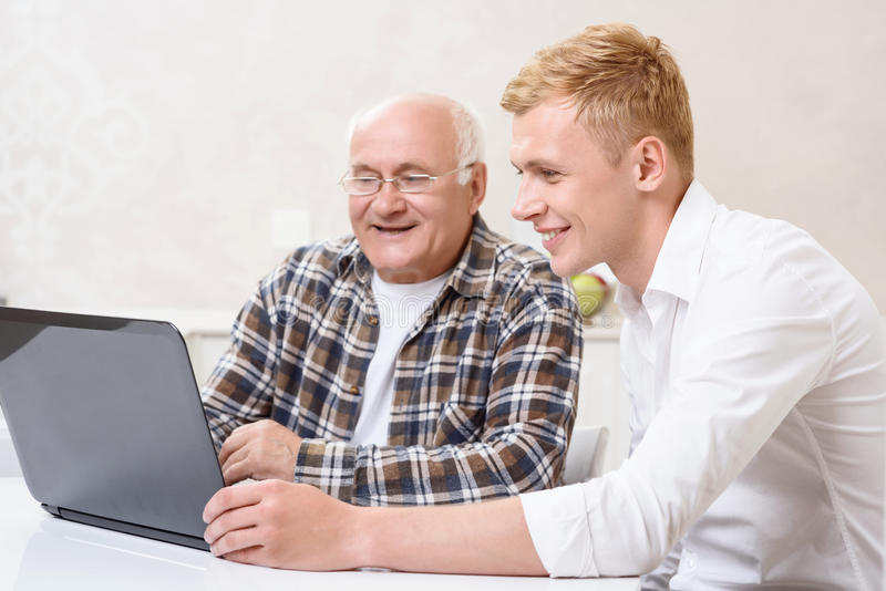 Grandfather and grandson sitting with laptop. Showing new technologies. Grandfather and grandson sitting together in kitchen and using laptop royalty free stock images