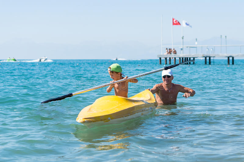 Grandfather and grandson smiling little baby boy in green baseball cap kayaking at tropical ocean sea in the day time. Positive h stock photos