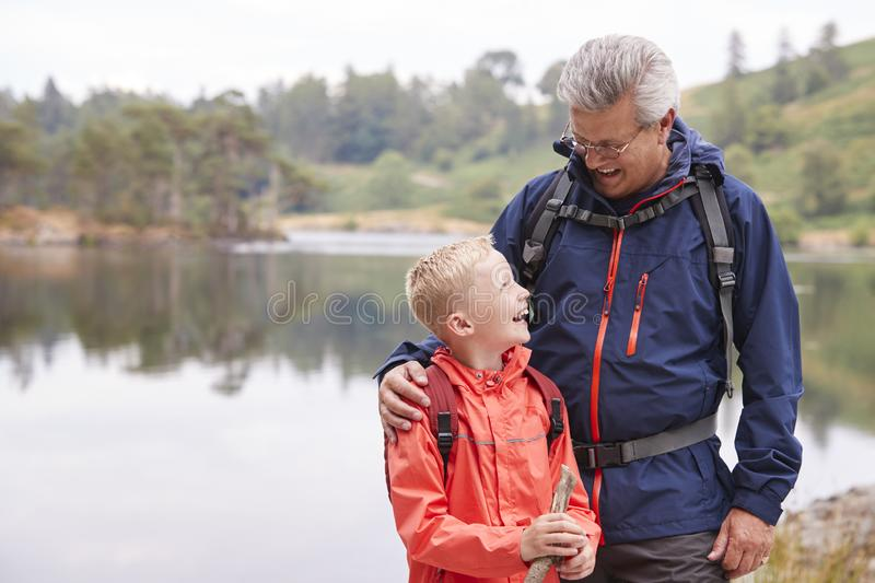 Grandfather and grandson standing on the shore of a lake looking at each other laughing, Lake District, UK royalty free stock images