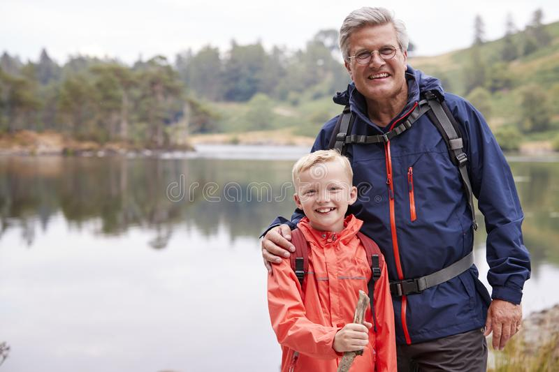 Grandfather and grandson standing together on the shore of a lake smiling to camera, close up, Lake District, UK stock images