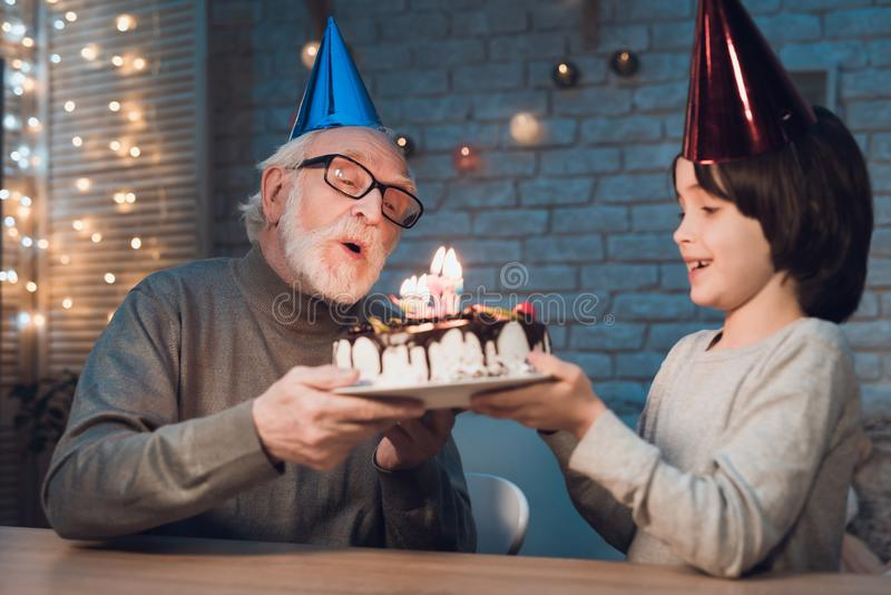 Grandfather and grandson at night at home. Birthday party. Granddad is giving boy birthday cake. Grandfather and grandson at table at night at home. Birthday stock photography
