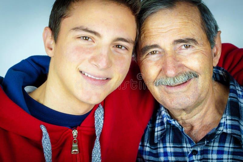 Grandfather and grandson. Teenage boy hugging grandfather royalty free stock image