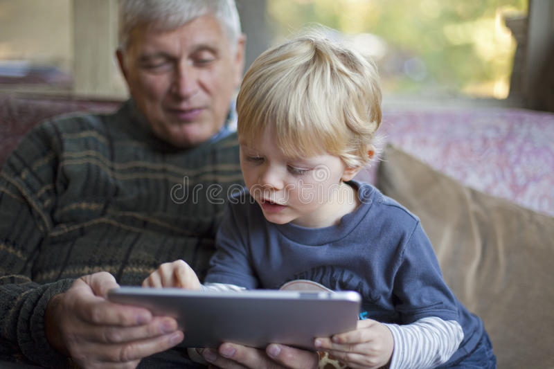 Grandfather and grandson using Tablet PC royalty free stock photography