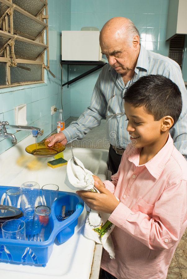 Grandfather and grandson washing dishes - Vertical royalty free stock photos