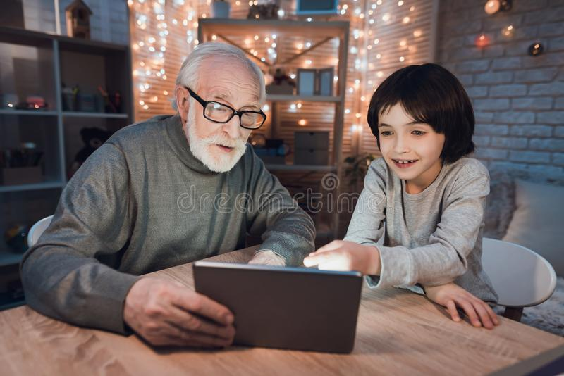 Grandfather and grandson are watching movie on tablet at night at home. Grandfather and grandson are watching movie on tablet at table at night at home stock image