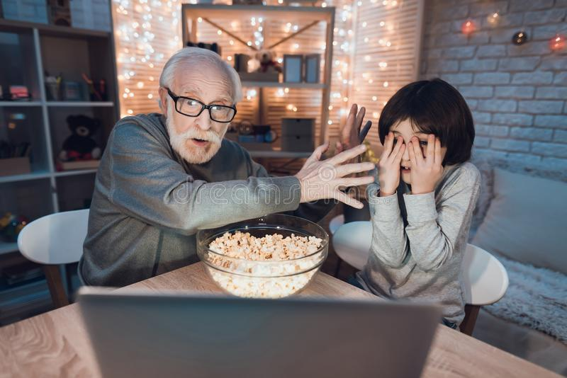 Grandfather and grandson are watching scary movie at night at home. stock photos